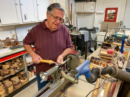 Dennis Dickey, owner of Triple D Woodworks, turns wood as he creates a limited edition pen from New Mexico State University's Lou Henson Court.