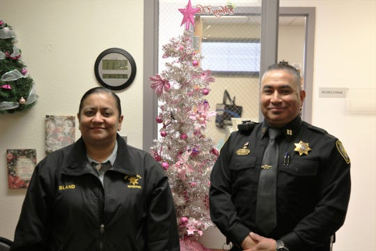 Joanne Bland and Capt. Michael Corona stand in front of a Christmas tree at the Eddy County Detention Center.