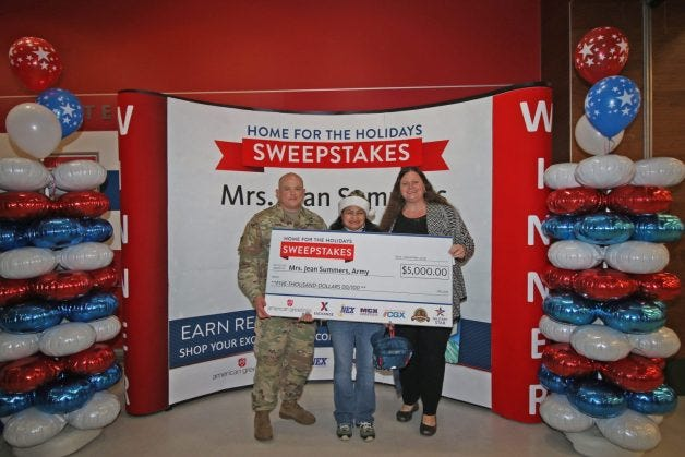Army spouse Jean Summers won $5,000 in the MILITARY STAR card's $25,000 Home for the Holidays Sweepstakes. From left are Fort Stewart Garrison Commander Col. Bryan Logan, Army sweepstakes winner Jean Summers and Fort Stewart Exchange General Manager Hollie Heft Morales.