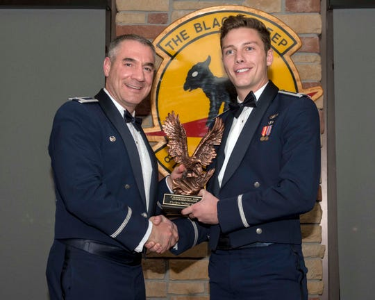 1st Lt Seth Bolon, 8th Fighter Squadron Basic Course graduate, accepts the Distinguished Graduate award during the graduation of B-Course Class 19-CBF, Dec. 14, 2019, on Holloman Air Force Base, N.M. 11 B-Course students graduated and will be reassigned to operational flying units throughout the combat Air Force.