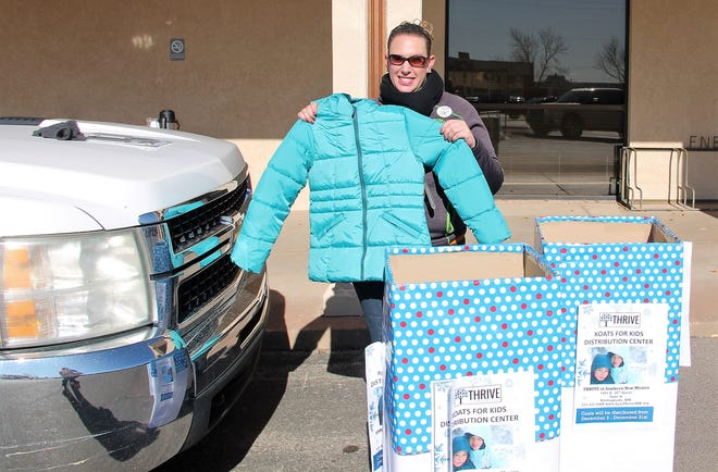 Thrive Director of Fundraising & Public Relations Stephanie Hale holds up one of the donated coats at the Thrive Koats for Kids coat drive event at First National Bank Dec. 20.