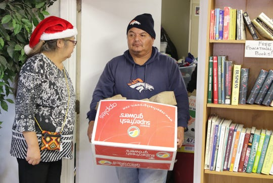 A volunteer for the Healing Circle Drop-In Center carries a box of items for the center's Christmas celebration on Dec. 19 in Shiprock.