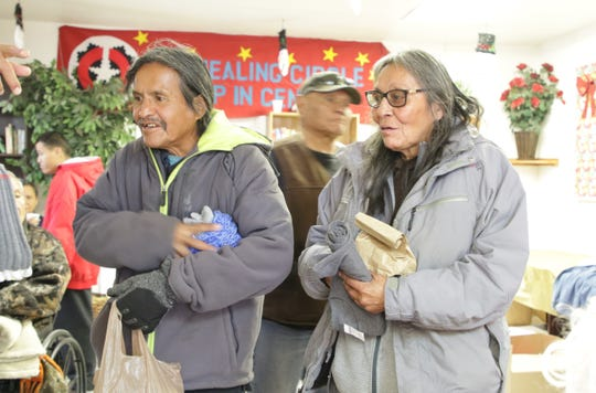 Two residents from Shiprock receive items at the Christmas celebration at the Healing Circle Drop-In Center on Dec. 19 in Shiprock.
