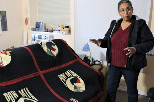 Navajo quilt artist Susan Hudson displays her quilt about native soldiers missing in action and prisoners of war at the artist's studio in Ignacio, Colorado on Dec. 18, 2019.