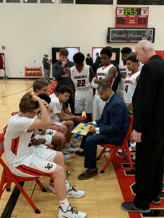 Livonia Churchill coach James McCulloh talks to his team during a timeout against Plymouth Christian.