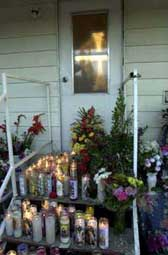Shrine: A steady stream of believers placed candles and flowers near a cross  that appeared Feb. 13, 2002, Ash Wednesday, on the door of a mobile home in Thermal.