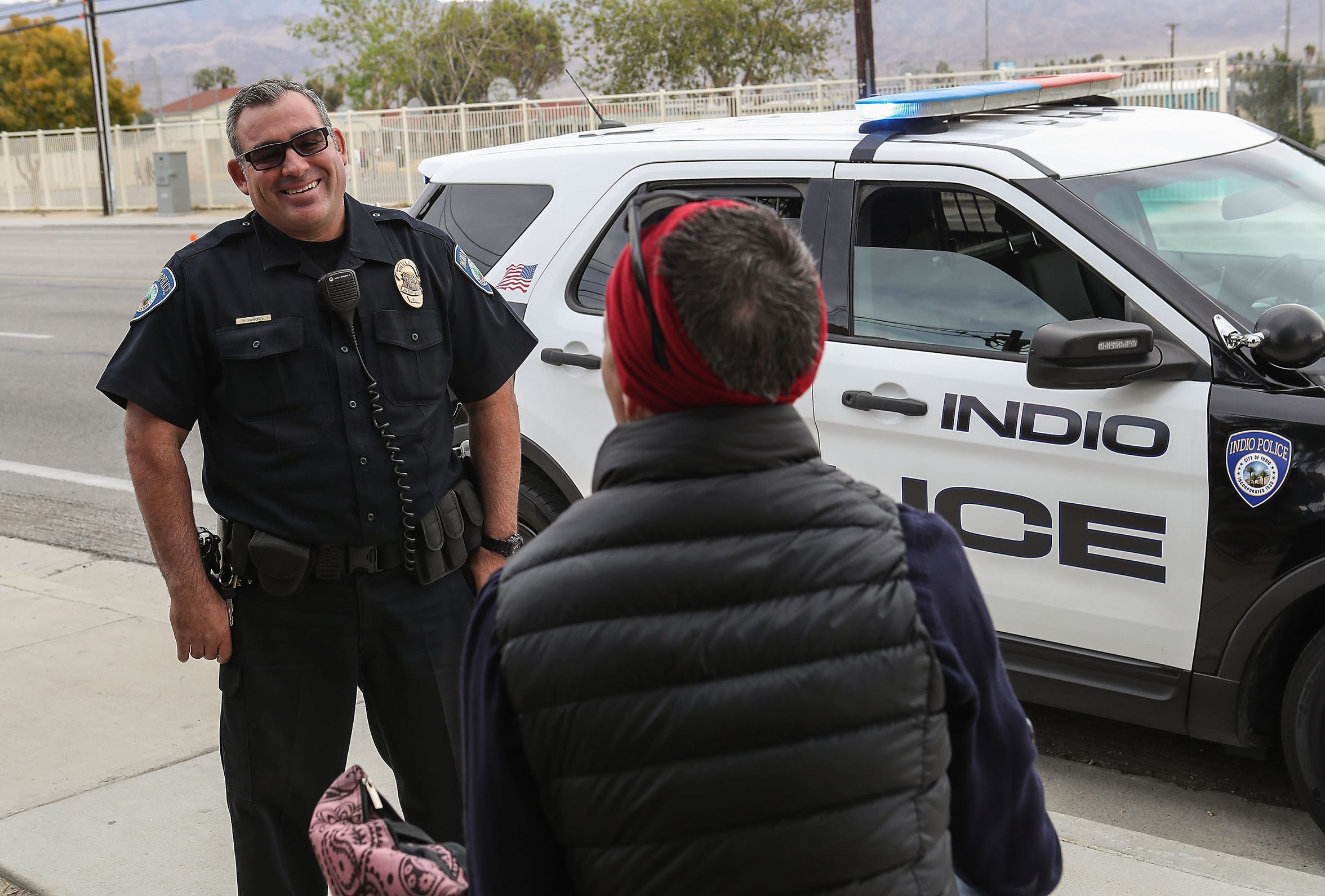 Indio Police Officer Brandon Haworth talks with Stephanie Goodson who had been homeless before finding housing in Indio, December 18, 2019.