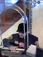 The bank robbery suspect was last seen wearing a green jumpsuit uniform and baseball hat.