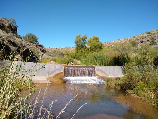 "Spring Creek flows over a concrete ""fish barrier,"" which was built to protect native fish, in the Coconino National Forest."