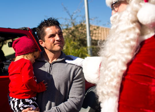 Santa thanks Justin Lopez for his service as a first responder on Dec. 20, 2019, in Goodyear. Lopez is a Peoria firefighter who was injured in April in an APS battery explosion in Surprise.