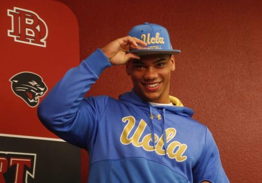 Desert Ridge's Joquarri Price puts on his hat after signing to play at UCLA inside Desert Ridge High School in Mesa, Ariz. on Dec. 20, 2019.