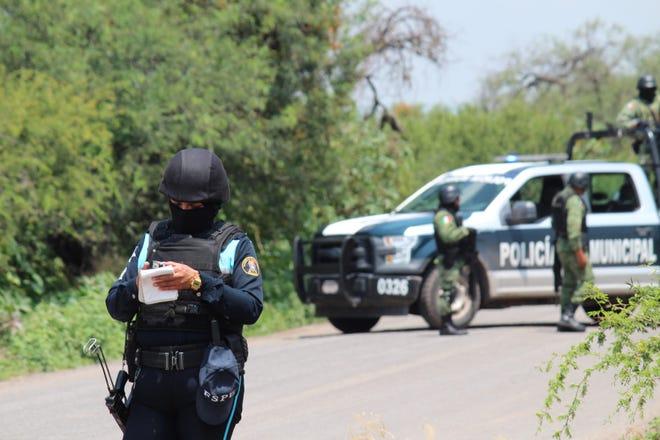 Policías prestan guardia en la zona donde un vehículo policial fue atacado por grupos armados, en Guanajuato (México).
