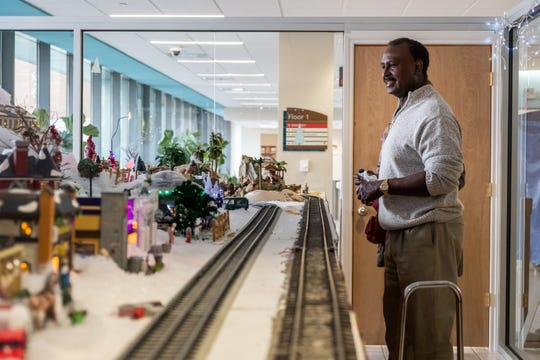 Percy McDonald, ear, nose and throat doctor at McLaren Port Huron, watches model trains run through his Christmas display Friday, Dec. 20, 2019, in the lobby at McLaren Port Huron. The display runs from 8 a.m. to 8 p.m.