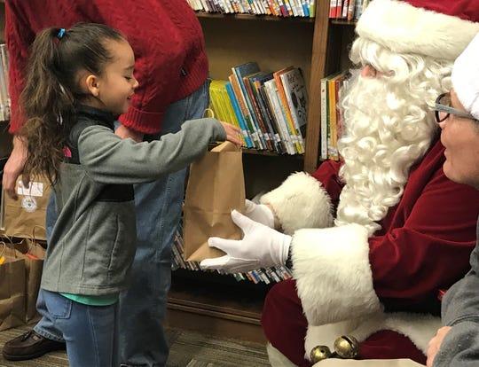 Luziris Martinez, a first-grader, receives her Wood to Wonderful gift from Santa Claus.