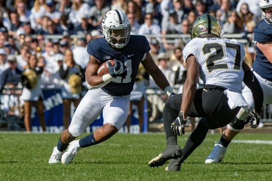 Oct 5, 2019; University Park, PA, USA; Penn State Nittany Lions running back Noah Cain (21) carries the ball against Purdue Boilermakers safety Navon Mosley (27) during the fourth quarter at Beaver Stadium. Mandatory Credit: John Jones-USA TODAY Sports