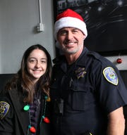 RPD Officer Tony Daniels poses for a portrait with his daughter Bella during the annual Reno Police Christmas Outreach on Dec. 20, 2019.