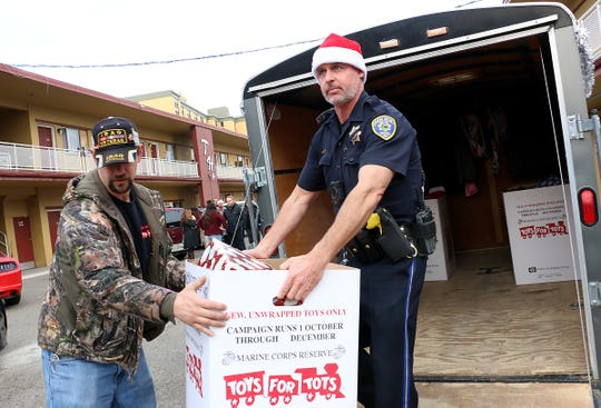 Reno Police Dept. Officer Tony Daniels, right, helps distribute toys at a local motel during the annual Reno Police Christmas Outreach on Dec. 20, 2019.