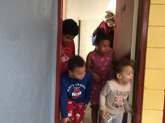 Children living at the Lake Mill Lodge look at presents being brought to them by Reno Police Department officers on Dec. 20, 2019.