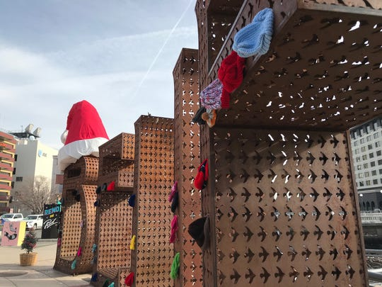 """A secret Santa hung warm hats for Reno's homeless population on the """"Believe"""" sign the morning of Dec. 20, 2019 in City Plaza."""