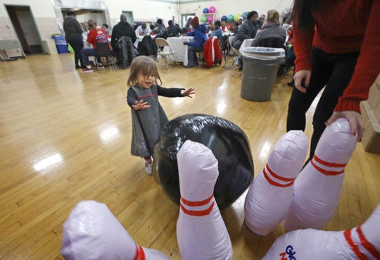 Ezrah Hilton, 2, sends inflated bowling pins flying as she plays at the Community Holiday Party at the Danforth Community Center.