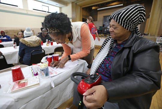 Sheila Rayam, Community Engagement Editor at the Democrat & Chronicle, signs a holiday stocking for Diana Mills, right, at the Community Holiday Party at the Danforth Community Center Thursday, Dec. 19, 2019.