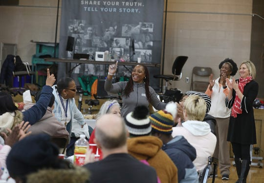 Karen Rogers, owner of Exercise Express, center, calls on audience members to offer what they were thankful for this holiday season before lunch was served at the Community Holiday Party at the Danforth Community Center, Thursday, Dec. 19, 2019.  The event, including a lunch, was put on by the Exercise Express and Samaritan Center Community.