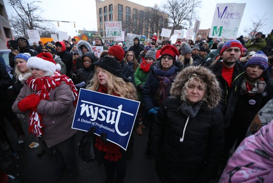 Over a hundred teachers and their supporters protest outside the Rochester City School District's Board of Education central administration office.