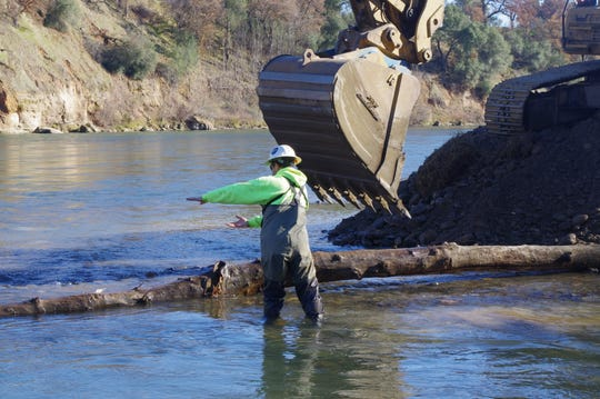 Aaron Martin, a habitat restoration biologist with the Yurok Tribe, shows an excavator operator where to place a log at a new channel for young fish at Anderson River Park.