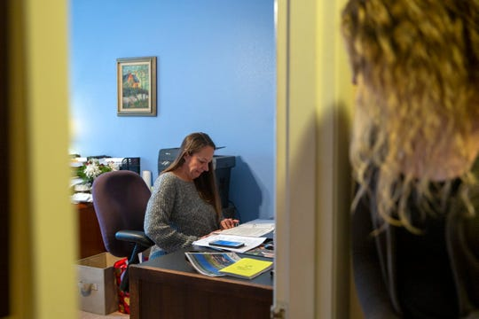 Executive Director Danica Thoren looks in at Kimberly Nowlin, an assistant case manager, at her desk in Grace House on Dec. 17, 2019. Women at the Well Grace House is a transitional shelter for women, some of whom flee domestic violence, sex trafficking, prostitution, or rape while homeless.