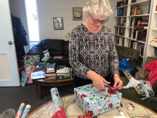 Sarah Hill wraps a Christmas present for a child in need after their gifts were stolen from their home.