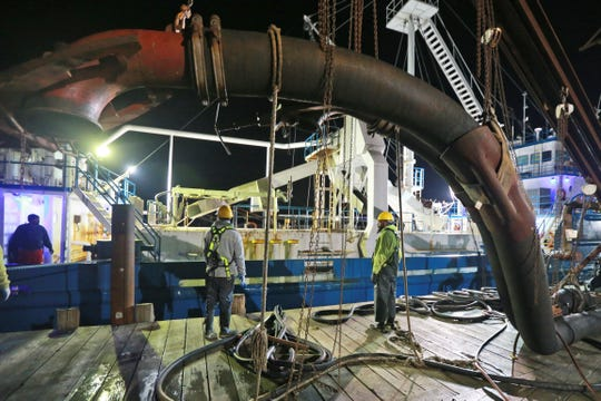 In this Tuesday, Nov. 26, 2019 photo, workers prepare to attach suction hose to the menhaden fishing boat Windmill Point at Omega Protein's menhaden processing plant on Cockrell's Creek in Reedville, Virginia.