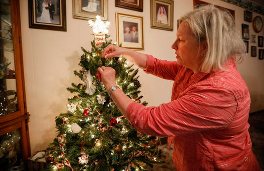 Debra Robinson puts an ornament on her tree that she made with newspaper and wrapping paper at her home in Springfield on Friday, Dec. 20, 2019.