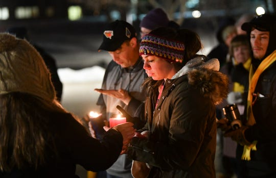 Candles are lit during a vigil for guardsmen James Rogers, Kort Plantenberg and Charles Nord Thursday, Dec. 19, 2019, at Lake George in St. Cloud.