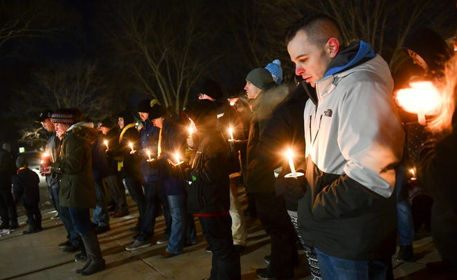 People hold candles during a vigil for guardsmen James Rogers, Kort Plantenberg and Charles Nord Thursday, Dec. 19, 2019, at Lake George in St. Cloud. The three soldiers were killed in a helicopter crash Dec. 5 near Marty.