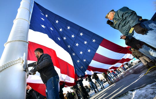 A 30-by-60-foot American flag is raised during a ceremony Friday at Minnesota Truck Headquarters Friday, Dec. 20, 2019, in St. Cloud. The business says the flagpole, at 150-feet tall is the tallest dedicated flagpole in Minnesota.
