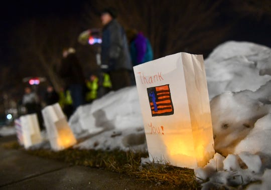 Luminaries line the sidewalk before the start of a candlelight vigil Thursday for guardsmen killed in a helicopter crash Dec. 5 at Lake George in St. Cloud.