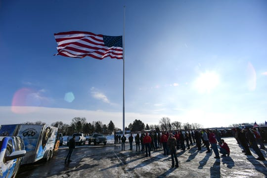A crowd gathers as the 30-by-60-foot American Flag is raised for the first time at Minnesota Truck Headquarters Friday, Dec. 20, 2019, in St. Cloud.
