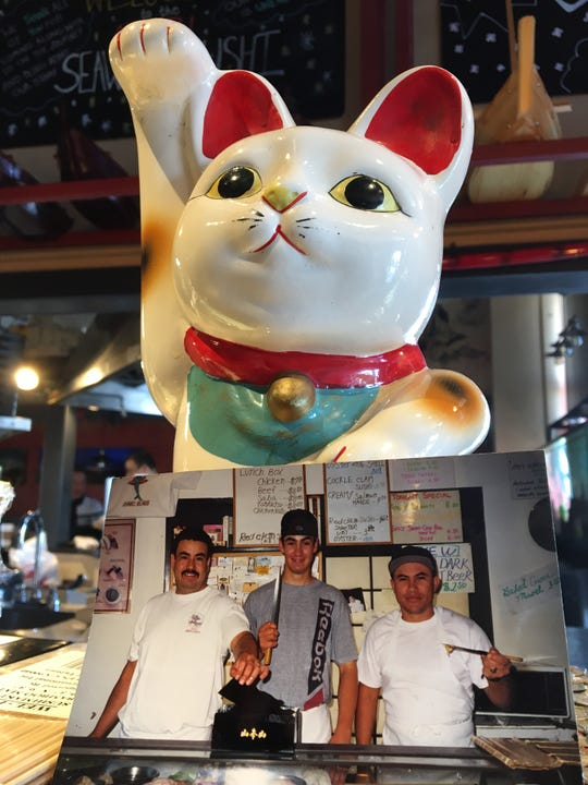 A 1990s-era photo of Gabriel Barrios, left, and Oscar Barrios, center, shows the brothers with a co-worker at the former Sushi Ichiban in Port Hueneme. It is displayed at the counter of Seaward Sushi in Ventura, which the brothers reopened this week as the new owners.