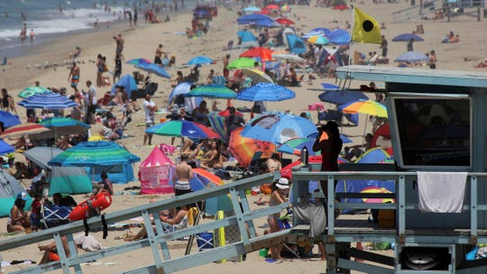 In this July 8, 2017, photo, a lifeguard scans a crowded Manhattan Beach shoreline. California's population has stalled at 39 million people, according to the latest figures.
