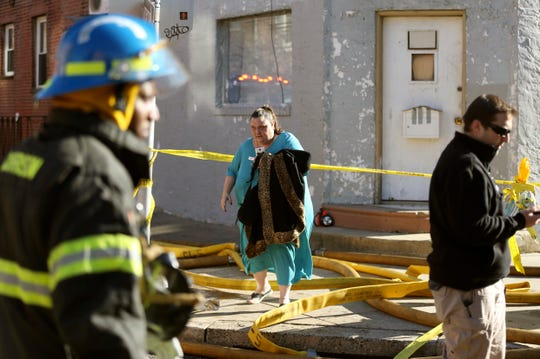 A woman is evacuated from a nearby home as firefighters battle a fire in Philadelphia on Thursday, Dec. 19, 2019. (Tim Tai/The Philadelphia Inquirer via AP)
