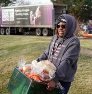 Iyonna Logan of Denver carries a box of food to her car after visiting a Food Bank of the Rockies distribution on Dec. 19, 2019. Logan said she planned to share the food with her family. The Trump administration is planning to cut food stamp benefits for hundreds of thousands of Americans, arguing the booming economy means people can get jobs instead of seeking public assistance. Poverty experts say the move will dramatically increase demand on food banks nationwide.