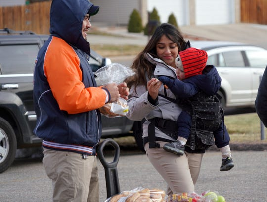 Gabriela and Brian Godoy feed their one-year-old son, Elian, bread after visiting a Food Bank of the Rockies food distribution in Denver on Dec. 19, 2019. The Trump administration is changing food stamp requirements in a move that poverty experts say will increase demand on food banks nationwide.
