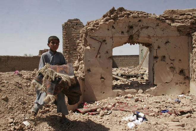 An Afghan boy carried a torn rug next to his destroyed home in Azizabad the day after the raid.