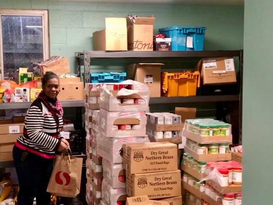 """A'Jay Scipio, the program manager of the Northeast Food Emergency Program in Portland, Oregon, walks through the food pantry in mid-December as she helps clients look for special Christmas treats. """"This is not a poor people problem,"""" Scipio says of the estimated 700,000 people who could lose their SNAP benefits in the spring. """"There are hard-working people, middle-class people, people with good jobs, who are hungry every day."""""""