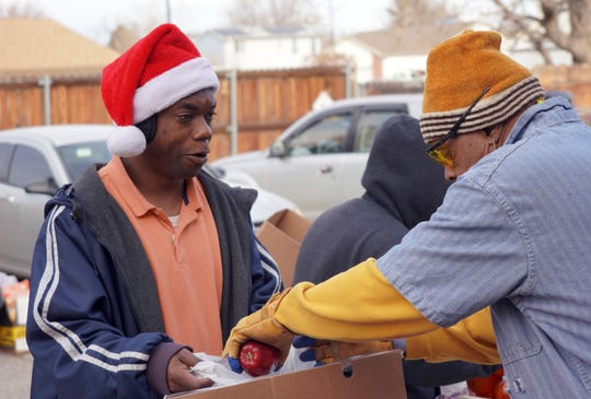 Resharde Law collects food for his family at a Food Bank of the Rockies distribution in Denver, Colorado, on Dec. 19. Law, who works as a mover, wore a Santa hat in an effort to spread cheer during the distribution.