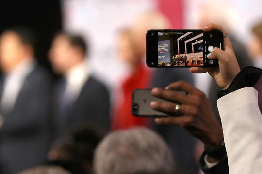 LOS ANGELES, CALIFORNIA - DECEMBER 19: Audience members take photos of the candidates on their phones ahead of the Democratic presidential primary debate at Loyola Marymount University on December 19, 2019 in Los Angeles, California. Seven candidates out of the crowded field qualified for the 6th and last Democratic presidential primary debate of 2019 hosted by PBS NewsHour and Politico. (Photo by Justin Sullivan/Getty Images) ORG XMIT: 775452704 ORIG FILE ID: 1194962125