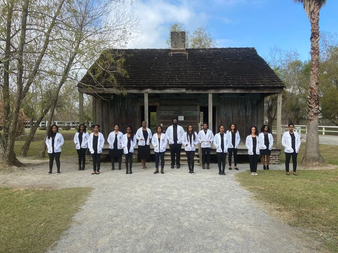 15 Tulane medical students pose in front of the slave quarters at the Whitney Plantation in Louisiana.