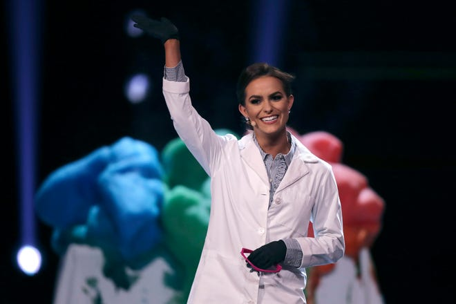 Camille Schrier, of Virginia, waves after performing a science experiment prior to winning the Miss America competition at the Mohegan Sun casino in Uncasville, Conn.