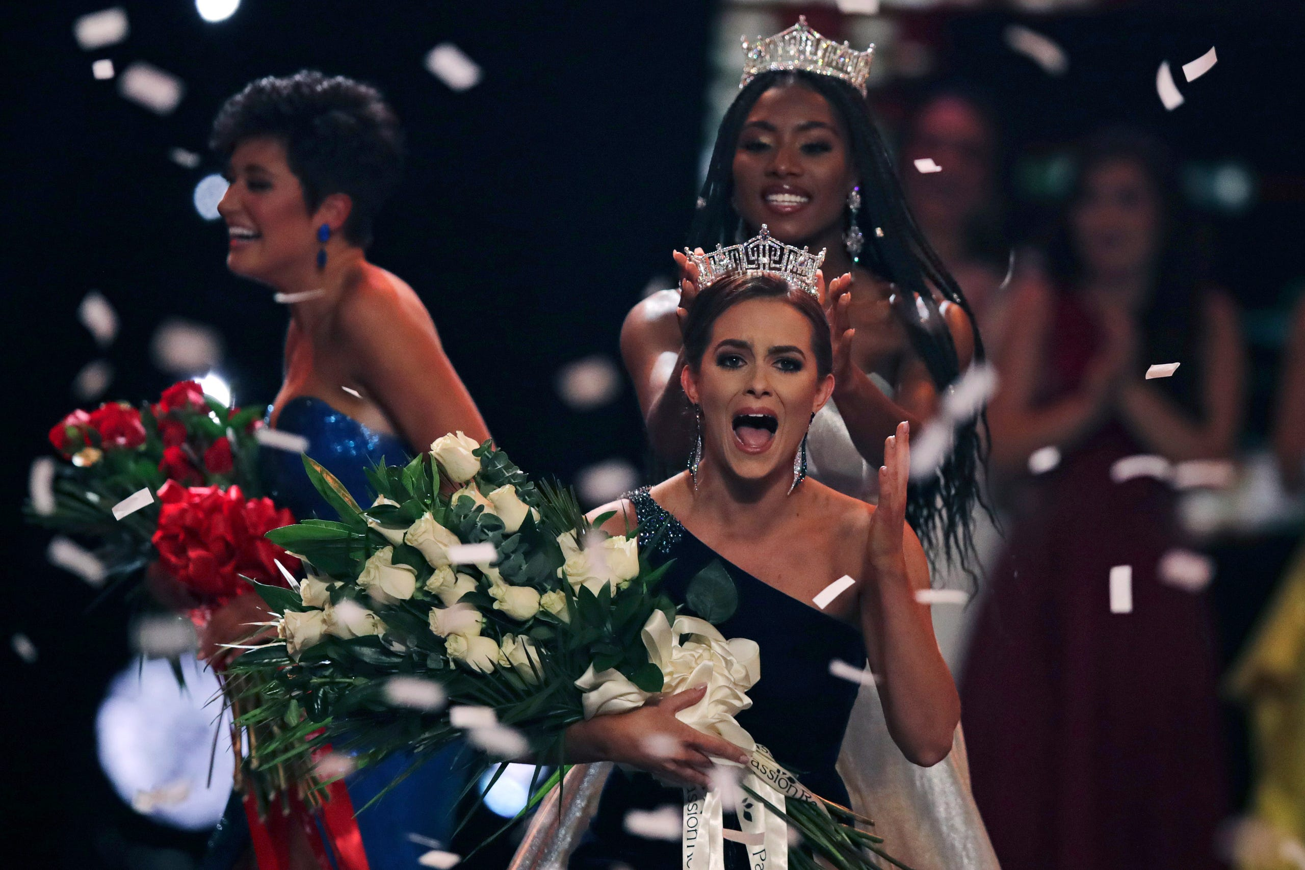 Camille Schrier, of Virginia, right, reacts after winning the Miss America competition at the Mohegan Sun casino in Uncasville, Conn., Thursday, Dec. 19, 2019. At left is runner-up Miss. Georgia Victoria Hill and at rear is Miss. America 2019 Nia Franklin. (AP Photo/Charles Krupa) ORG XMIT: CTCK106