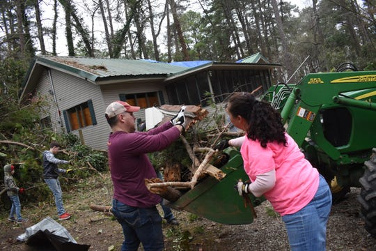 Lyndon Marcotte (left) and Lee Dufour help learn away debris from John Foster Gunter's property in Pineville. Gunter's house and out buildings sustained damage after a tornado came through the area Monday.